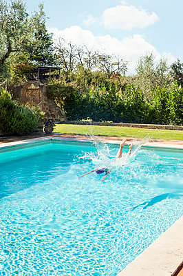 Woman diving into swimming pool - p352m2120197 by Anna Larsson
