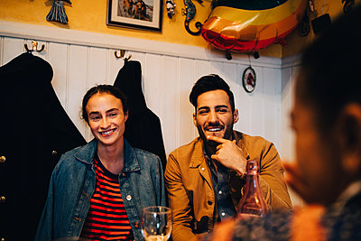 Smiling young man and woman looking at female friend during dinner party at restaurant - p426m2046285 by Maskot