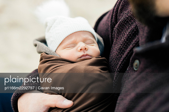 A newborn baby bundled up and in his father's arms - p1166m2292797 by Cavan Images