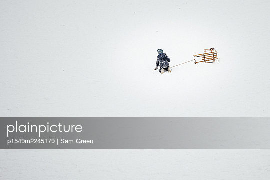 Toddler with sledge in the snow - p1549m2245179 by Sam Green