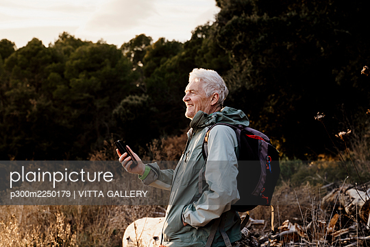 Smiling senior man with mobile phone looking away while standing in filed during weekend - p300m2250179 by VITTA GALLERY