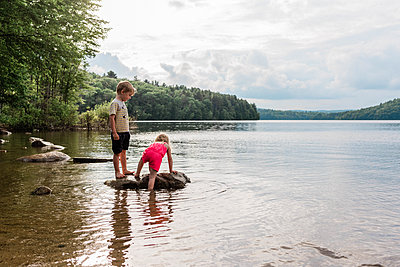 Little kids standing on a rock surrounded by water. - p1166m2162947 by Cavan Images