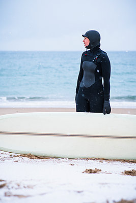Young woman going winter surfing in snow - p1166m2177041 by Cavan Images