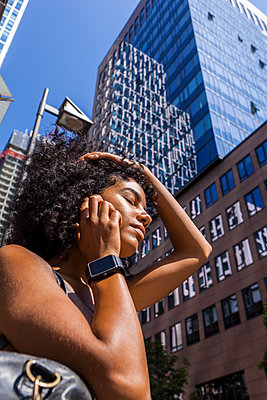 Germany, Frankfurt, portrait of young woman with smartwatch on the phone in front of skyscrapers - p300m2030323 by Tom Chance