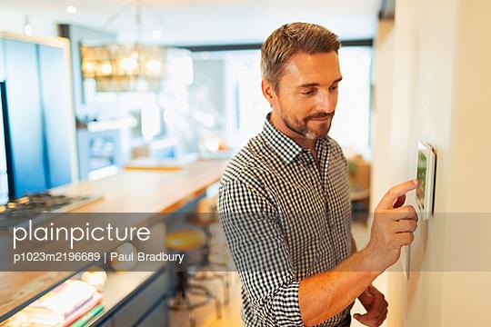 Man adjusting digital home automation thermostat - p1023m2196689 by Paul Bradbury