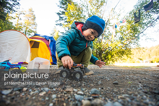 Toddler boy driving monster trucks through dirt and rocks. - p1166m2147337 by Cavan Images