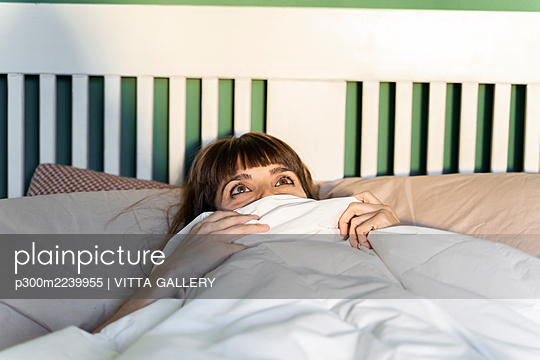 Woman looking away while lying on bed at home - p300m2239955 by VITTA GALLERY