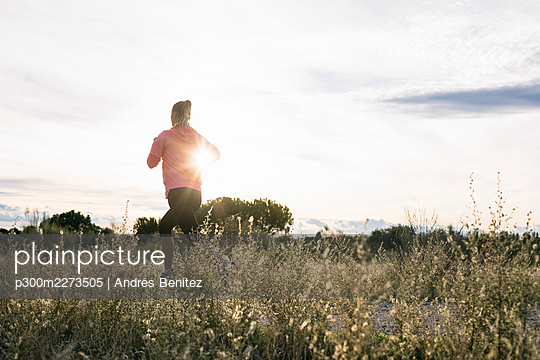 Female jogger running by agricultural field during sunny day - p300m2273505 by Andrés Benitez