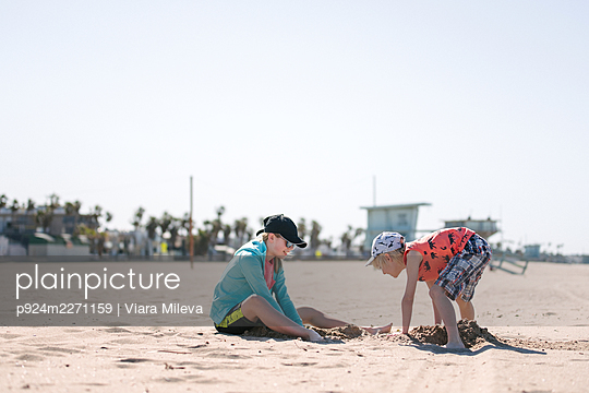 Sister and brother playing in sand on beach - p924m2271159 by Viara Mileva