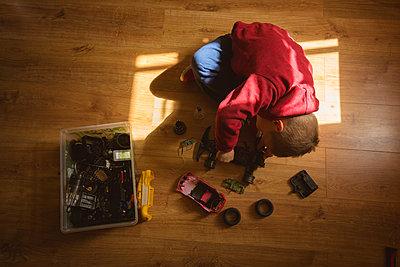 Little boy repairing toy car in bedroom - p1315m2018459 by Wavebreak