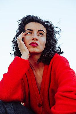 Porträt einer jungen verträumten Frau in roter Strickjacke - p1363m2175831 von Valery Skurydin