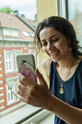 Junge Frau mit Smartphone - p1611m2182303 von Bernd Lucka