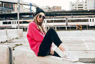 Portrait of fashionable young woman wearing sunglasses, cap and pink knit pullover - p300m2078661 by Aitor Carrera Porté