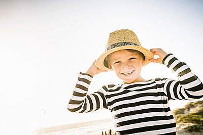 Portrait of happy boy with hat on the beach - p300m2167083 by Floco Images