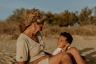 Grandmother and grandson sitting on sand at beach during sunset - p300m2220770 by Eloisa Ramos