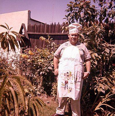 Caucasian man standing in yard wearing chef hat and apron - p555m1444173 by PBNJ Productions