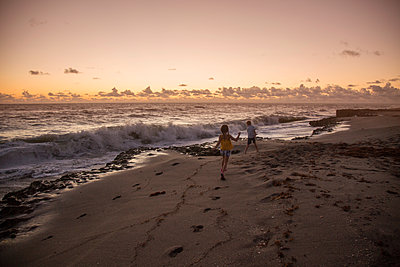 Boy and sister running on beach at sunrise, Blowing Rocks Preserve, Jupiter Island, Florida, USA - p924m1157658 by Kinzie Riehm