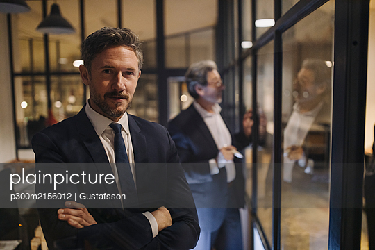 Portrait of confident businessman with colleague drawing on glass pane in office - p300m2156012 by Gustafsson