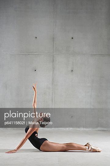 Ballet dancer posing on floor