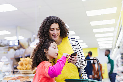 Mother and daughter with smart phone shopping in supermarket - p1023m2187672 by Sam Edwards