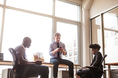 Business people using communication device while sitting at office - p1166m1099079f by Cavan Images