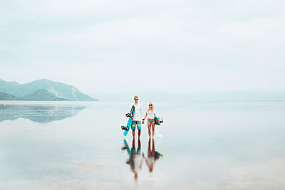 Couple with surfboard standing in sea against sky during foggy weather - p1166m1544853 by Cavan Social