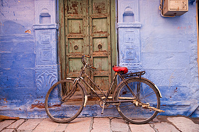 India, Rajasthan, Jodhpur, bicycle leaning at blue facade in the old town - p300m1017669 by Peter Schickert