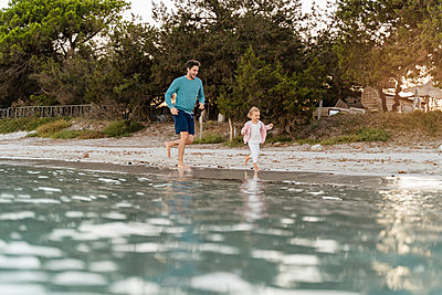 Happy father running with daughter on the seashore - p300m2143685 by Daniel Ingold