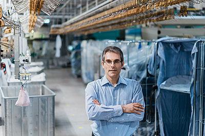 Portrait of a confident mature businessman in a laumdry shop - p300m2197496 by Daniel Ingold