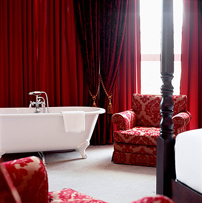 Contemporary red decorated bedroom with upholstered armchair and bath tub  - p349m695157 by Emma Lee