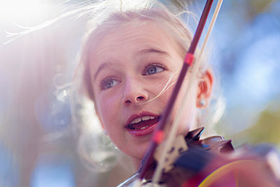 Close up of Caucasian girl playing violin - p555m1410222 by Marc Romanelli