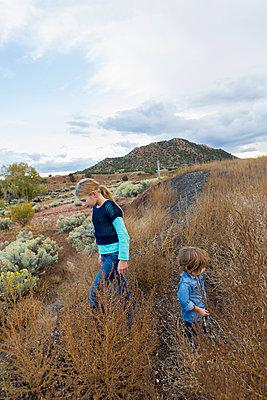 Caucasian children exploring hillside - p555m1410475 by Marc Romanelli