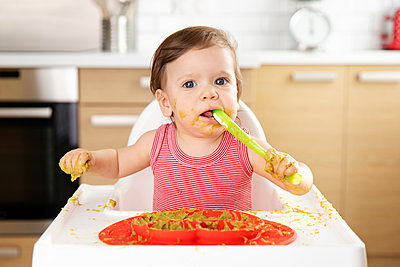 Baby in high chair eating pea puree with spoon - p1166m2084904 by Cavan Images