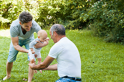 Senior man spending time with his adult son and his granddaughter in a park - p300m2188367 by Daniel Ingold