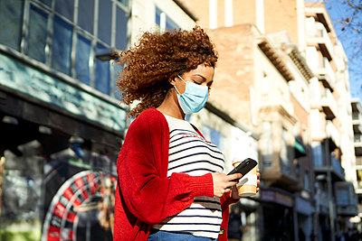 Curly hair woman wearing sanitary mask holding coffee cup while using mobile phone standing in city - p300m2257345 by Veam