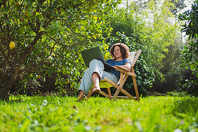 Smiling woman looking at laptop while sitting on chair in permaculture garden - p300m2267376 by Steve Brookland