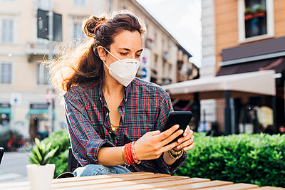 Woman with protective face mask using mobile phone at sidewalk cafe on sunny day - p300m2293991 by Eugenio Marongiu