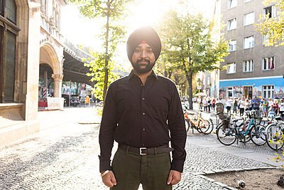 Indian man exploring city, bicycles in background, Berlin, Germany - p429m2077802 by Tamboly