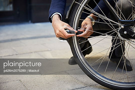 Low section of male commuter locking electric bicycle wheel against building in city - p426m2075289 by Maskot