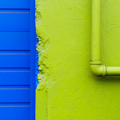 A green painted wall and pipe by a blue doorway.  - p1100m876206f by Paul Edmondson