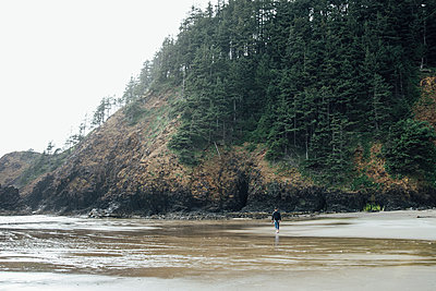 Rear view of man walking on shore at beach against hill - p1166m1524556 by Cavan Images