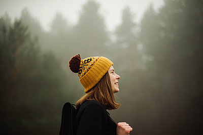 Thoughtful woman standing by forest in foggy weather - p1166m2151796 by Cavan Images