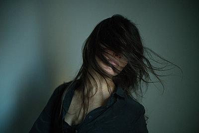 Wind bläst Haar das Haar einer Frau ins Gesicht - p1321m2126134 von Gordon Spooner