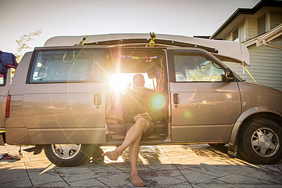 Barefoot man sitting in minivan in backlight using cell phone - p300m1568015 by Gustafsson