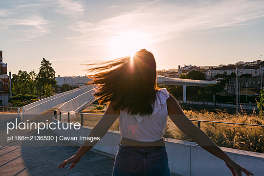 Woman with sun-flare. - p1166m2136590 by Cavan Images