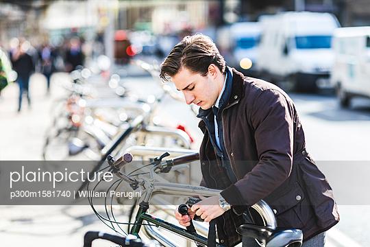 Businessman locking bicycle in the city - p300m1581740 von William Perugini