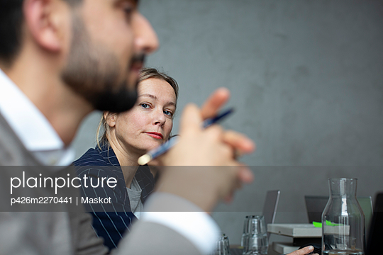 Businesswoman with male colleague in discussion during meeting at creative office - p426m2270441 by Maskot