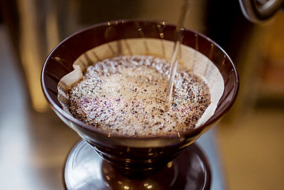 Water being poured on coffee filter at cafe - p1166m1144821 by Cavan Images