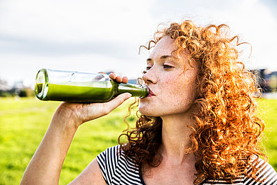 Portrait of redheaded young woman drinking beverage - p300m2028966 by Jo Kirchherr