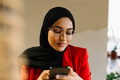 Woman wearing hijab smiling while using mobile phone in coffee shop - p300m2282719 by Xavier Lorenzo